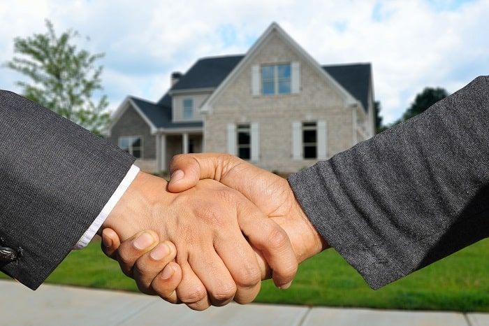 shaking hands in front of house