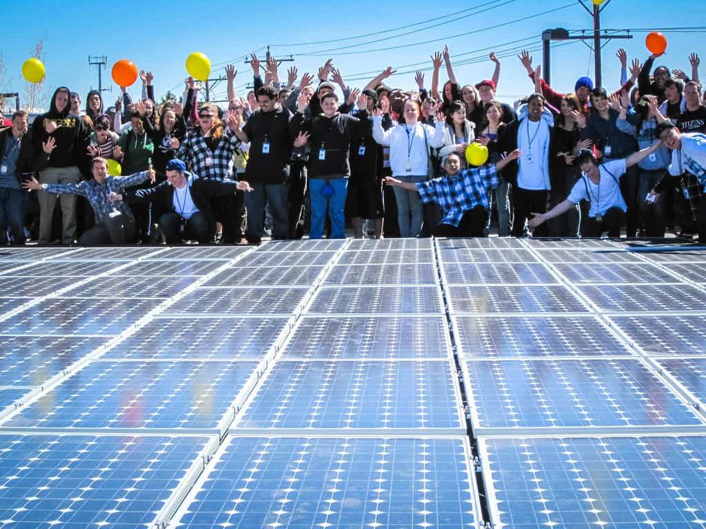 school children gather around a bank of solar panels